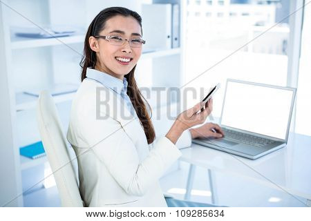 Smiling businesswoman using smartphone and laptop at the desk in work