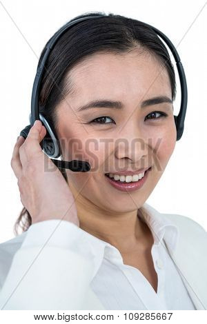 Smiling businesswoman using headset against white background