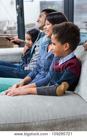 Happy young family watching tv in living room