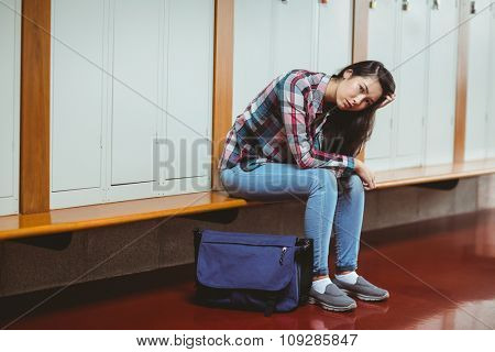 Worried student sitting with hand on head at the university