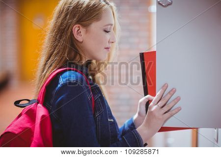 Pretty student with backpack putting notebook in the locker at the university
