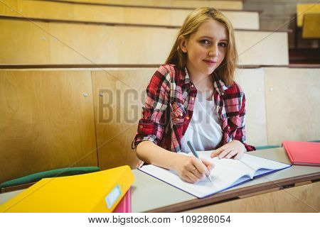 Smiling student taking notes during class at the university