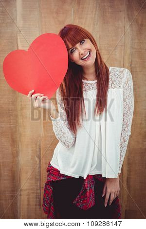 Smiling hipster woman with a big red heart against wooden background