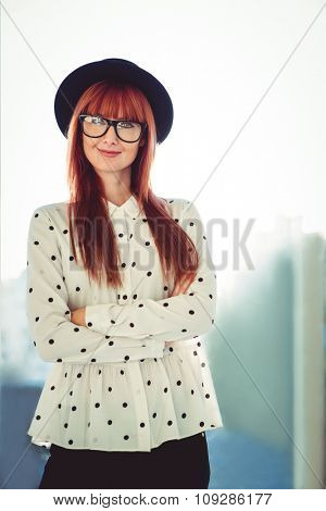 Portrait of a smiling hipster woman with arms crossed in a bright room