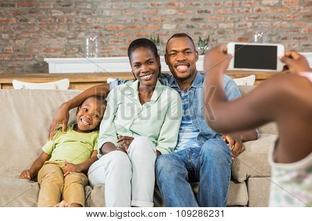 Happy family taking a picture on the couch in living room