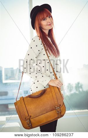 Portrait of a smiling hipster woman with a bag in a bright room