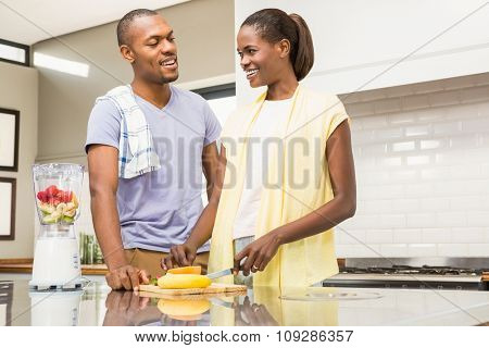 Young casual couple making fruits in the kitchen
