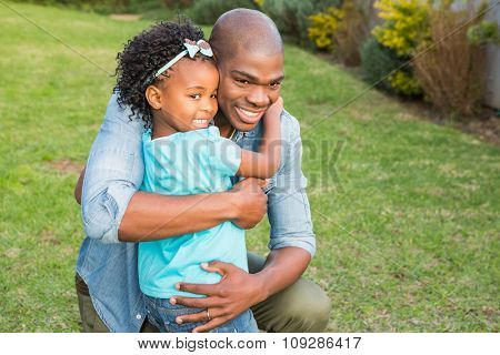 Smiling father hugging his daughter in the garden
