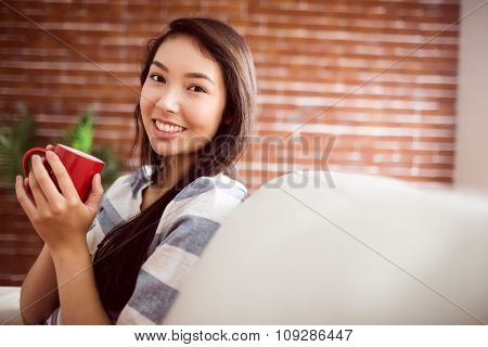 Smiling asian woman on couch having hot drink at home in the living room