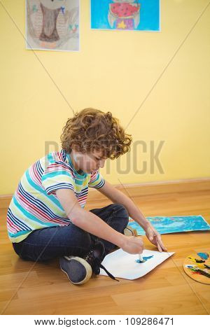 Small boy painting on some paper on the floor