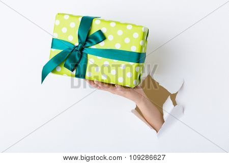 Hand through the hole in paper with present box
