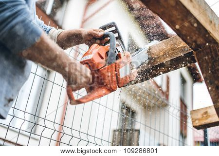 Worker Using An Industrial Chainsaw For Cutting Timber Wood At Construction Site