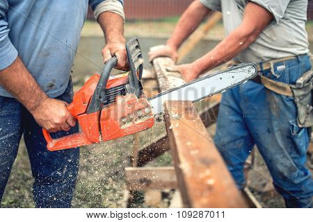 Workers, Handymen Cutting Timber Wood Using Mechanical Chainsaw.