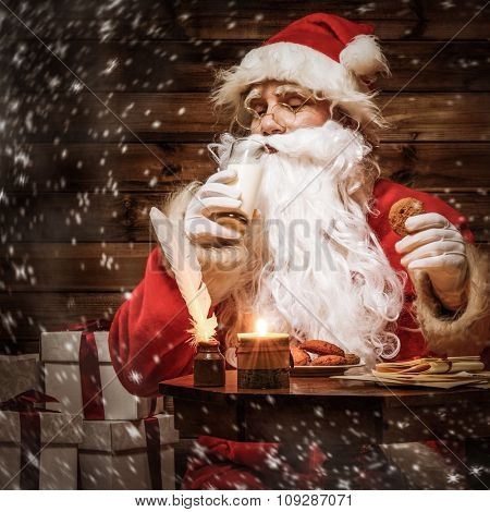 Santa Claus  in wooden home interior with glass of milk and oatmeal cookies