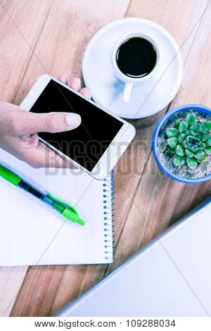 Overhead of feminine hand holding smartphone with notebook, laptop and black espresso on table