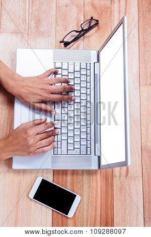 Overhead of female hands typing on laptop with glasses and smartphone on desk