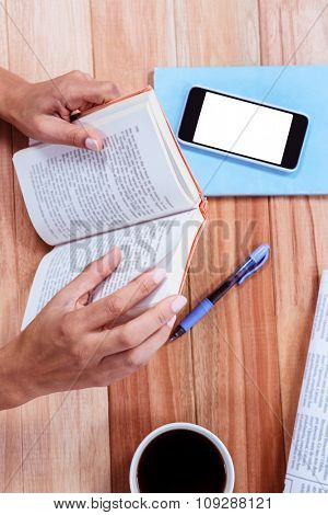 Overhead of feminine hands holding a book and with coffee, newspaper and smartphone on table