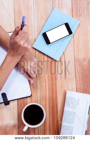 Overhead of feminine hands holding a pen with coffee, newspaper and smartphone on table