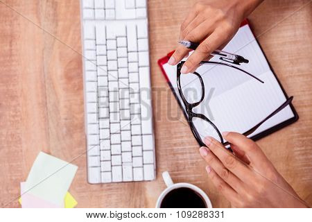 Businesswoman holding pen and eye glasses on desk