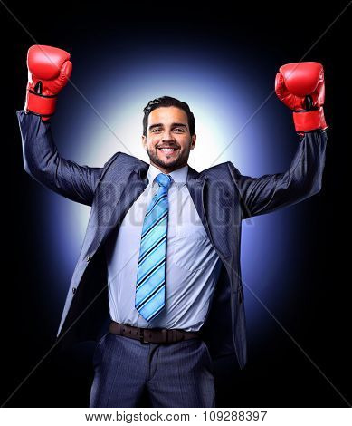 Businessman in a suit and boxing gloves, celebrating a win