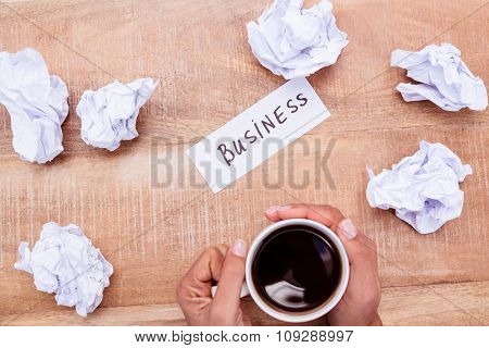 Businesswoman holding black coffee cup on desk