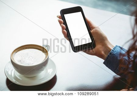 Woman taking a photo of her coffee at the university