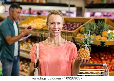 Smiling woman holding a pineapple at the grocery