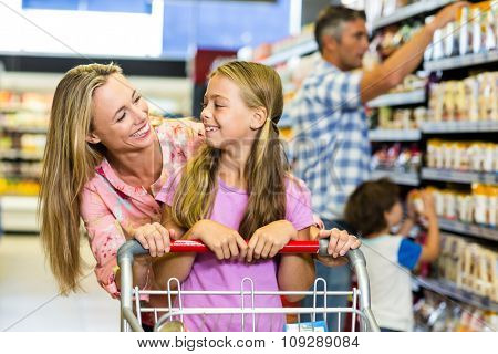 Smiling mother and daughter at the supermarket
