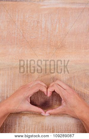 View of hands making heart shape on wooden desk