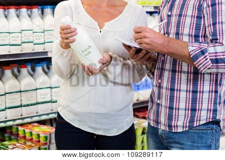 Smiling couple buying milk and checking list at the supermarket