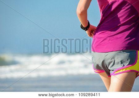 Woman running on beach, beautiful girl runner jogging outdoors, training for marathon, exercising