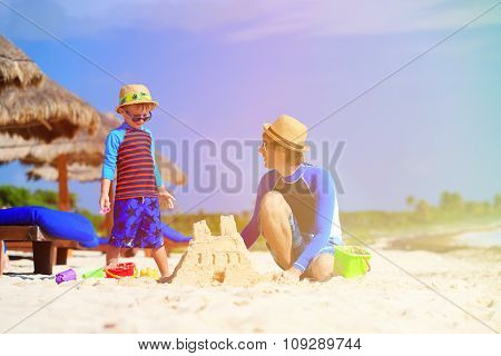 father and son building sand castle on beach