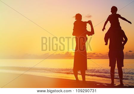 happy family with two kids having fun on sunset beach