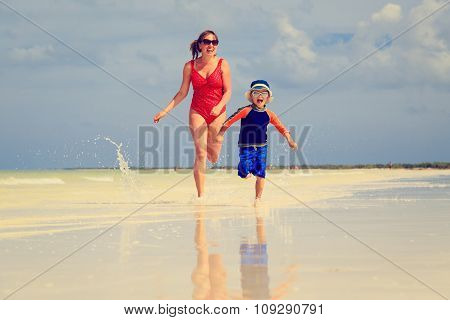 mother and son running in water on beach