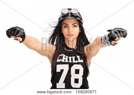 Studio shot of a female biker with helmet and goggles pretending to ride a motorcycle isolated on white background