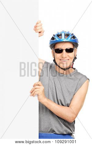 Vertical shot of a senior cyclist with sunglasses posing behind a blank signboard isolated on white background