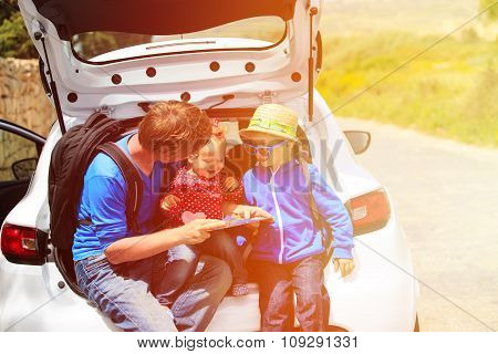 father with two kids looking at map while travel