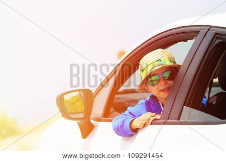 happy little boy travel by car on the road