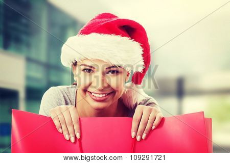 Beautiful woman wearing santa hat, holding shopping bag