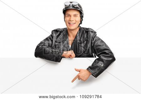Young biker in a black leather jacket standing behind a blank billboard and pointing towards it with his finger isolated on white background