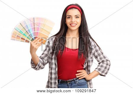 Studio shot of a young woman holding a color swatch and looking at the camera isolated on white background