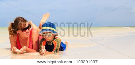 mother and son having fun with water at beach