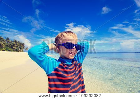 happy boy in swimming goggles on beach