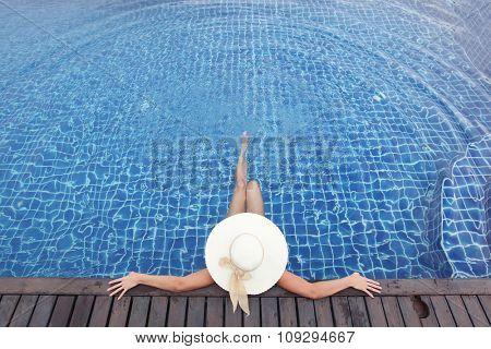 Woman in big hat relaxing in swimming pool
