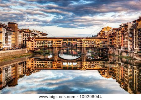 Ponte Vecchio bridge in Florence, Italy. Arno River. Tuscany under sunset romantic sky, clouds
