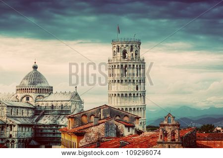 Pisa Cathedral with the Leaning Tower panorama. Unique vintage perspestive from rooftop, dark clouds. Tuscany, Italy