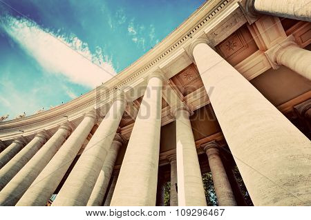 St. Peter's Basilica colonnades, columns in Vatican City. Blue sky, vintage