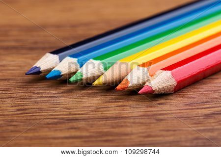 Coloured crayons on wood background, school colorful crayons