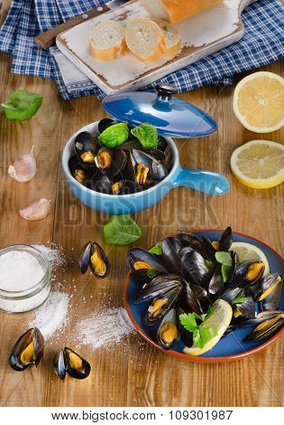 Plates Of Steamed Mussels On Wooden Background.