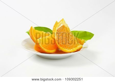 plate of sliced orange with leaves on white background
